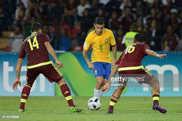 Philippe Coutinho of Brazil fights for the ball with Arles Flores and Roberto Rosales of Venezuela during a match between Venezuela and Brazil as...