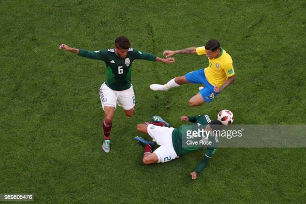 Philippe Coutinho of Brazil is tackled by Hugo Ayala and Jonathan Dos Santos of Mexico during the 2018 FIFA World Cup Russia Round of 16 match...