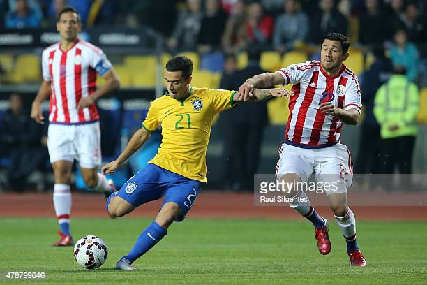 Philippe Coutinho of Brazil kicks the ball followed by Eduardo Aranda of Paraguay during the 2015 Copa America Chile quarter final match between...
