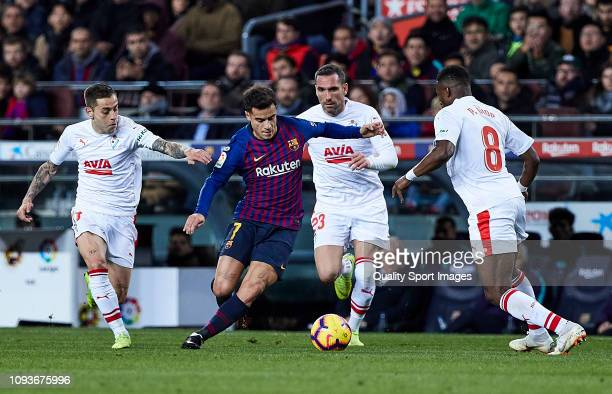 Philippe Coutinho of FC Barcelona competes for the ball with Pape Diop Marc Cardona and Anaitz Arbilla of SD Eibar during the La Liga match between...