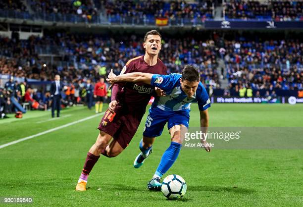 Philippe Coutinho of FC Barcelona duels for the ball with Federico Ricca of Malaga during the La Liga match between Malaga and Barcelona at Estadio...