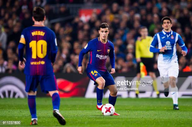 Philippe Coutinho of FC Barcelona passes the ball to his teammate Lionel Messi during the Spanish Copa del Rey Quarter Final Second Leg match between...