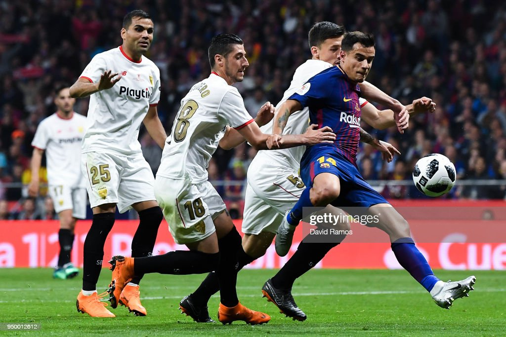 Philippe Coutinho of FC Barcelona scores a disallowed goal under a challenge from Sevilla FC players during the Spanish Copa del Rey Final match between Barcelona and Sevilla at Wanda Metropolitano stadium on April 21, 2018 in Barcelona, Spain.