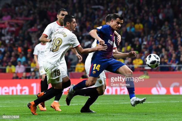 Philippe Coutinho of FC Barcelona scores a disallowed goal under a challenge from Sevilla FC players during the Spanish Copa del Rey Final match...