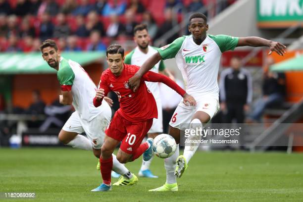 Philippe Coutinho of FC Bayern Munich is challenged by Reece Oxford of FC Augsburg during the Bundesliga match between FC Augsburg and FC Bayern...