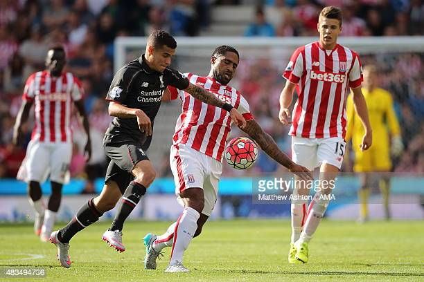 Philippe Coutinho of Liverpool and Glen Johnson of Stoke City battle for the ball during the Barclays Premier League match between Stoke City and...