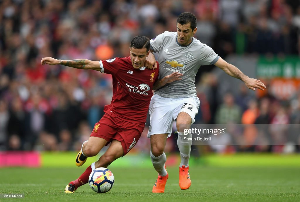 Philippe Coutinho of Liverpool and Henrikh Mkhitaryan of Manchester United battle for possession during the Premier League match between Liverpool and Manchester United at Anfield on October 14, 2017 in Liverpool, England.