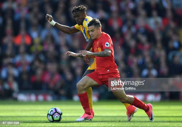 Philippe Coutinho of Liverpool and Wilfried Zaha of Crystal Palace compete for the ball during the Premier League match between Liverpool and Crystal...