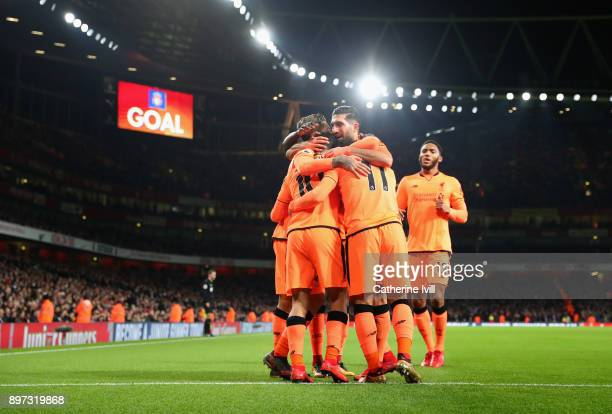 Philippe Coutinho of Liverpool celebrates as he scores their first goal with team mates during the Premier League match between Arsenal and Liverpool...
