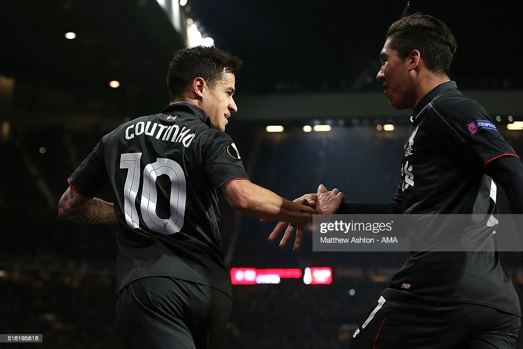 Philippe Coutinho of Liverpool celebrates scoring his team's first goal with team-mate Roberto Firmino (R) during the UEFA Europa League Round of 16 Second Leg match between Manchester United and Liverpool at Old Trafford on March 17, 2016 in Manchester, England.