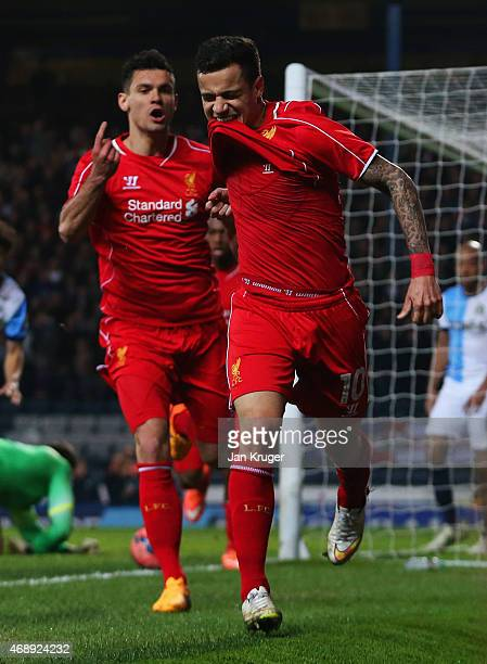 Philippe Coutinho of Liverpool celebrates with Dejan Lovren as he scores their first goal during the FA Cup Quarter Final Replay match between...