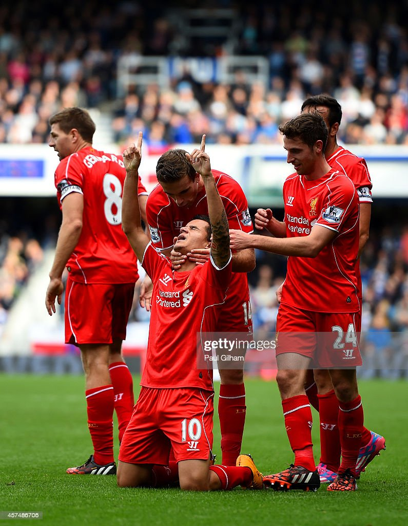 Philippe Coutinho of Liverpool celebrates with team-mates after scoring his team's second goal during the Barclays Premier League match between Queens Park Rangers and Liverpool at Loftus Road on October 19, 2014 in London, England.