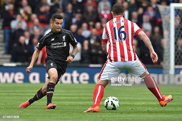 Philippe Coutinho of Liverpool competes with Charlie Adam of Stoke City during the Barclays Premier League match between Stoke City and Liverpool at...