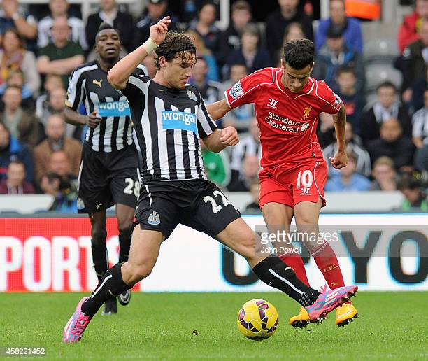 Philippe Coutinho of Liverpool competes with Daryl Janmaat of Newcastle United during the Barclays Premier League match between Newcastle United and...