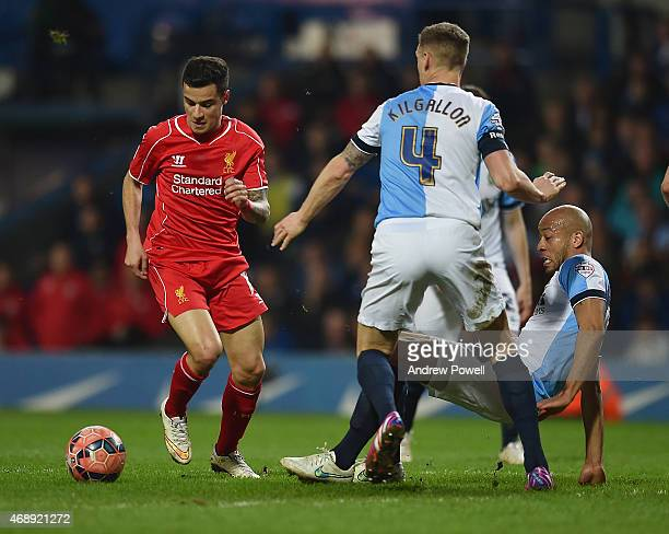 Philippe Coutinho of Liverpool competes with Matt Kilgallon of Blackburn Rovers during the FA Cup Quarter Final Replay match between Blackburn Rovers...