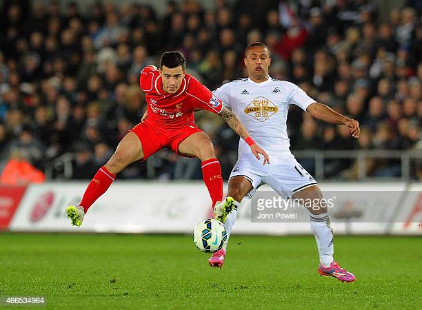 Philippe Coutinho of Liverpool competes with Wayne Routledge of Swansea City during the Barclays Premier League match between Swansea City and...