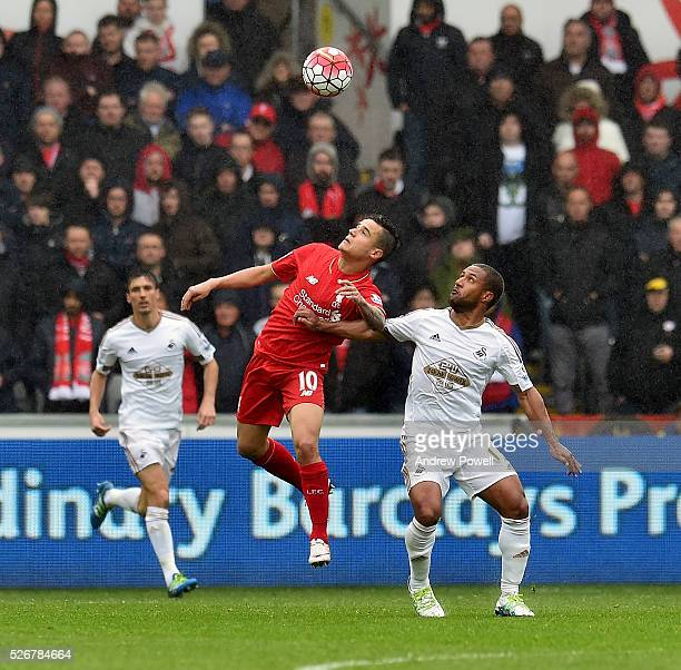 Philippe Coutinho of Liverpool competes with Wayne Routledge of Swansea City during a Premier League match between Swansea City and Liverpool at the...