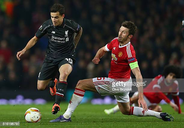 Philippe Coutinho of Liverpool evades Michael Carrick of Manchester United during the UEFA Europa League round of 16 second leg match between...