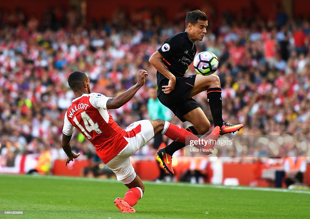 Philippe Coutinho of Liverpool is challenged by Theo Walcott of Arsenal during the Premier League match between Arsenal and Liverpool at Emirates Stadium on August 14, 2016 in London, England.