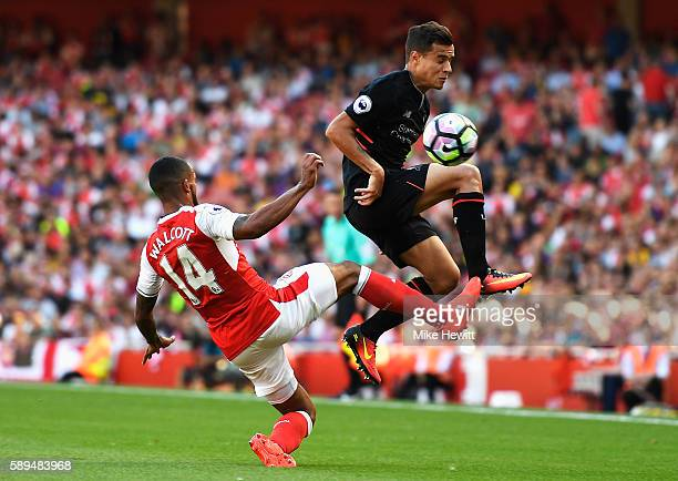 Philippe Coutinho of Liverpool is challenged by Theo Walcott of Arsenal during the Premier League match between Arsenal and Liverpool at Emirates...
