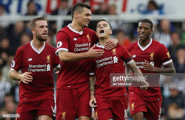Philippe Coutinho of Liverpool is congratulated by team mates after he scores the opening goal during the Premier League match between Newcastle...