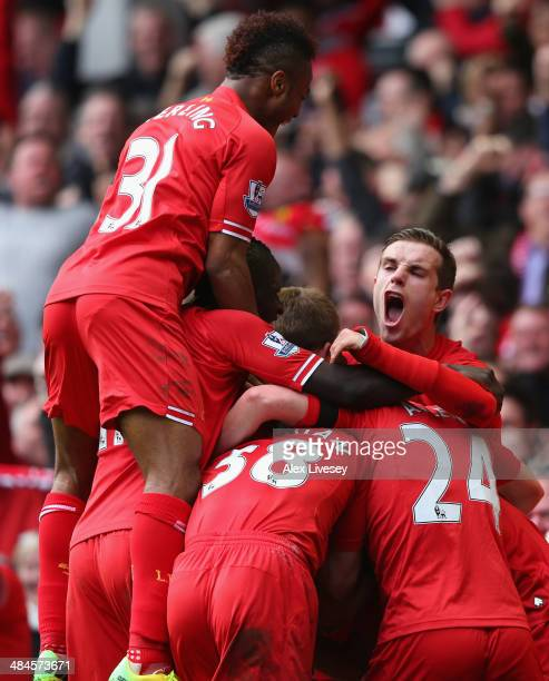 Philippe Coutinho of Liverpool is mobbed by his teammates after scoring his team's third goal during the Barclays Premier League match between...