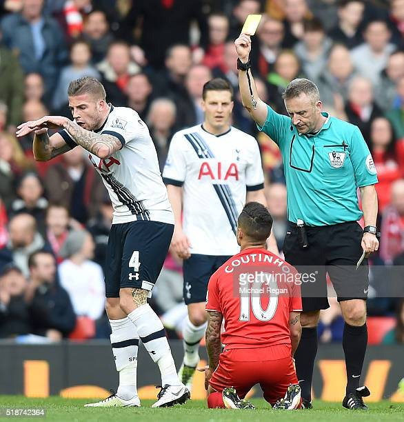 Philippe Coutinho of Liverpool is shown a yellow card by referee Jonathan Moss while Toby Alderweireld of Tottenham Hotspur gestures during the...