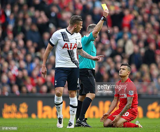 Philippe Coutinho of Liverpool is shown a yellow card by referee Jonathan Moss during the Barclays Premier League match between Liverpool and...
