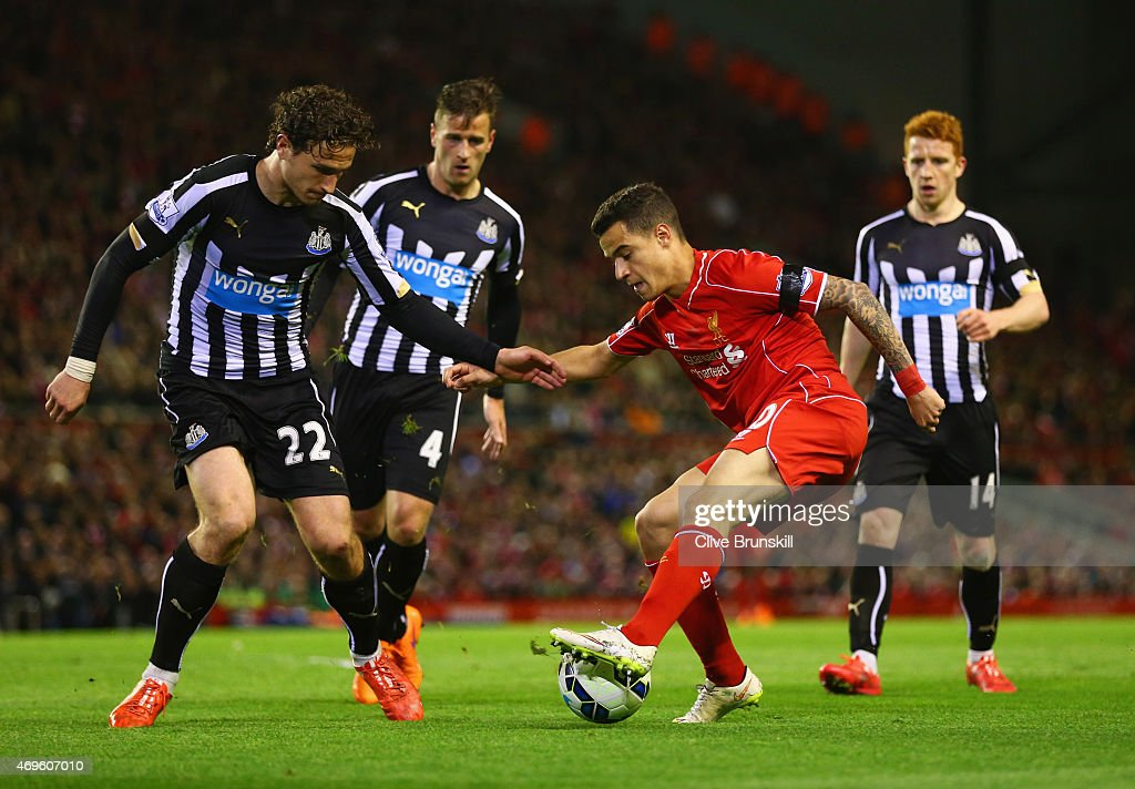 Philippe Coutinho of Liverpool is watched by Ryan Taylor (4) and Daryl Janmaat (22) and Jack Colback of Newcastle United (14) during the Barclays Premier League match between Liverpool and Newcastle United at Anfield on April 13, 2015 in Liverpool, England.