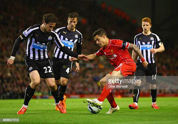Philippe Coutinho of Liverpool is watched by Ryan Taylor and Daryl Janmaat and Jack Colback of Newcastle United during the Barclays Premier League...