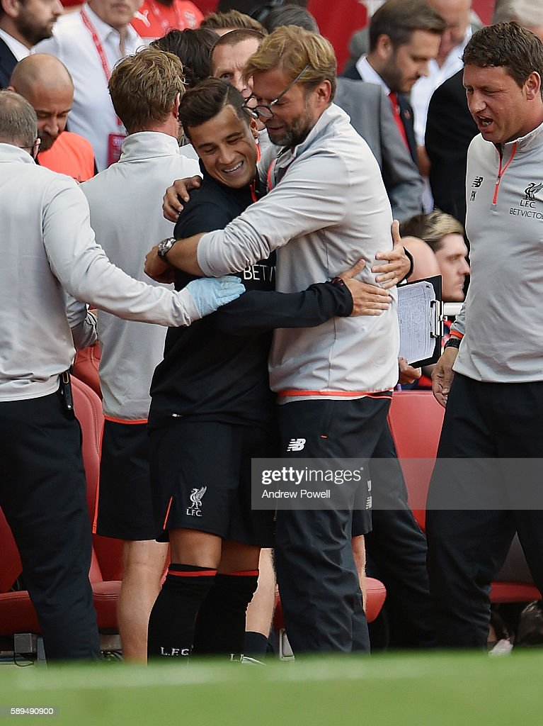 Philippe Coutinho of Liverpool knocks the glasses of his manager Jurgen Klopp during the Premier League match between Arsenal and Liverpool at Emirates Stadium on August 14, 2016 in London, England.