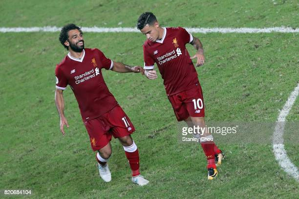 Philippe Coutinho of Liverpool reels away after scoring while Mohamed Salah runs to embrace him during the Premier League Asia Trophy match between...