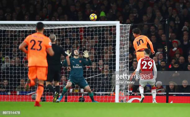 Philippe Coutinho of Liverpool scores their first goal past goalkeeper Petr Cech of Arsenal during the Premier League match between Arsenal and...