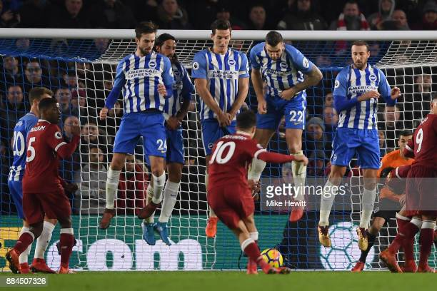 Philippe Coutinho of Liverpool slides the ball under the Brighton wall and into the net during the Premier League match between Brighton and Hove...