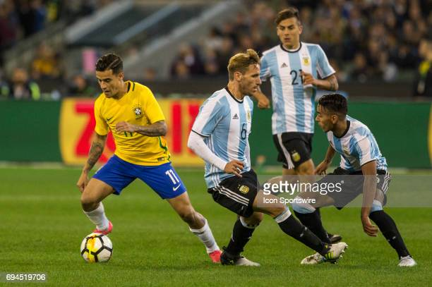 Philippe Coutinho of the Brazilian National Football Team controls the ball in front of Lucas Biglia of the Argentinan National Football Team and...