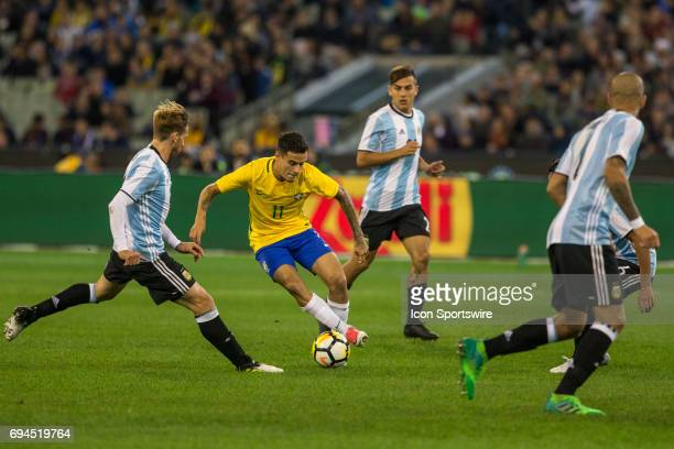 Philippe Coutinho of the Brazilian National Football Team controls the ball in front of Lucas Biglia of the Argentinan National Football Team during...