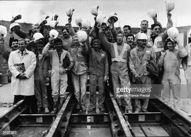 Philippe Cozette Roger Graham Fag and a construction crew pose during a ceremony marking the meeting of the English side and the French in the...