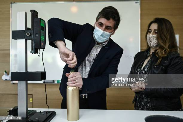 """Philippe Darriet, Director of the Oenology Research Unit Institute of Vines, Science and Wine opens an """"anonymised"""" bottle of Petrus before being..."""