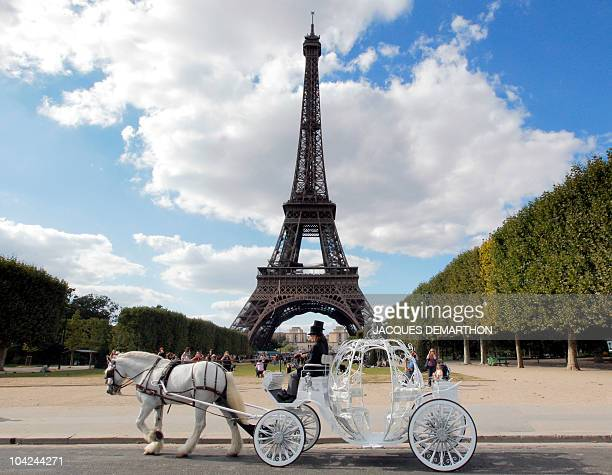 Philippe Delon owner of 'Paris Carriages Horse Walking Service' next to a groom drives a pumpkinshaped carriage drawn by Balthazar an 11yearold shire...