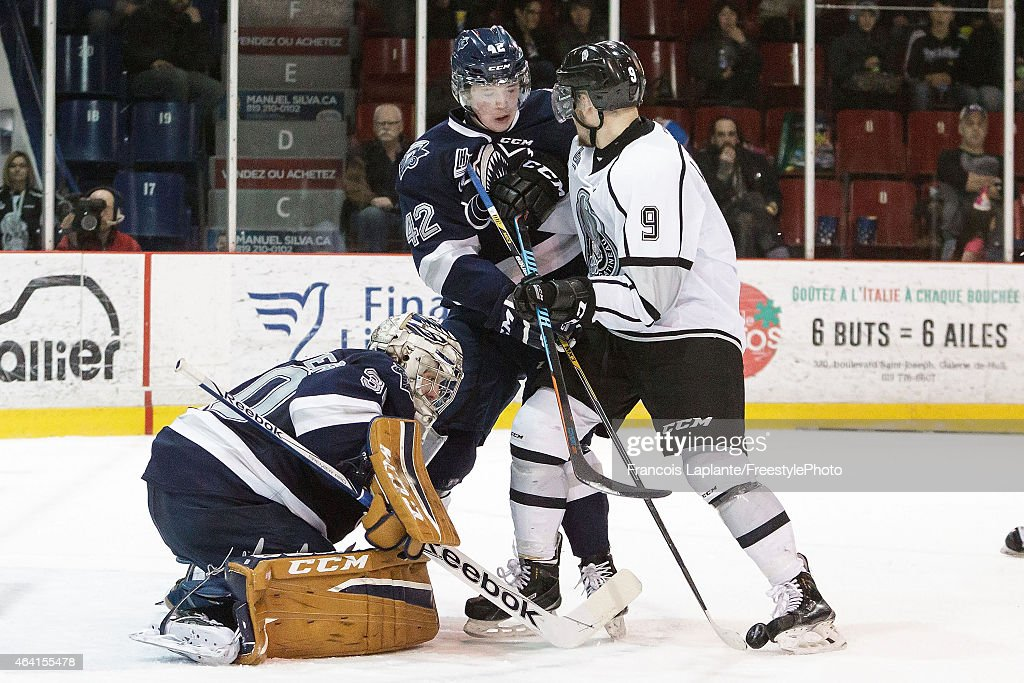 Philippe Desrosiers #30 of the Rimouski Oceanic keeps track of a inbound shot as Andrew Picco #42 defends against Yan Pavel Laplante #9 of the Gatineau Olympiques on February 22, 2015 at Robert Guertin Arena in Gatineau, Quebec, Canada.