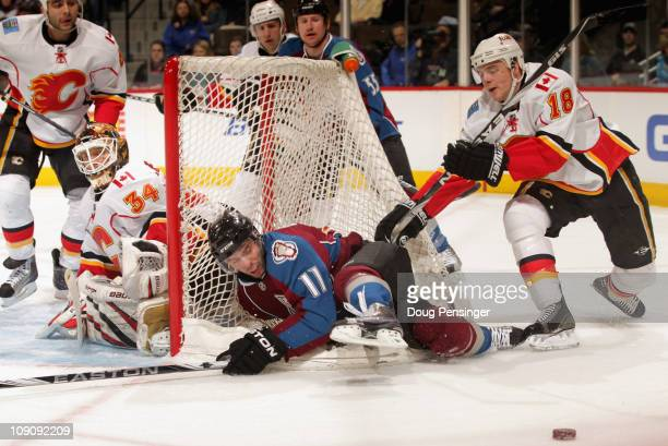 Philippe Dupuis of the Colorado Avalanche is checked into the back of the goal by Matt Stajan of the Calgary Flames as goalie Mikka Kiprusoff of the...