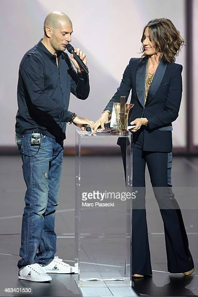 Philippe Fragione aka Akhenaton receives from Virginie Guilhaume the urban music award for the album 'Je suis en vie' during the 30th 'Victoires de...