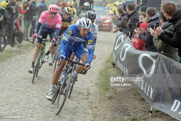 Philippe Gilbert rides the cobblestones sector 9 of Pont Thibaut in Ennevelin during the 117th Paris - Roubaix 2019 race from Compiegne to Roubaix on...