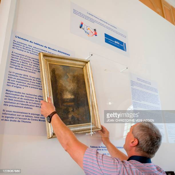 Philippe Hansch, director of the World Peace Center, hangs on August 17 in Verdun, the painting by the French painter Nicolas Rousseau, returned to...