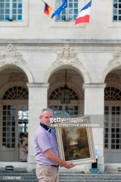 Philippe Hansch, director of the World Peace Center, presents on August 17 in Verdun, a painting by the French painter Nicolas Rousseau, restored to...