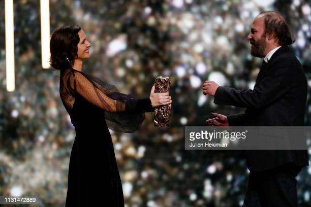 Philippe Katerine receives the Best Supporting Actor Award for the movie Le Grand Bain from Virginie Ledoyen during the Cesar Film Awards 2019 at...