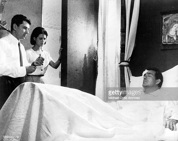 Philippe Nicaud and Claudia Cardinale standing at the bed of Ugo Tognazzi in a scene from the film 'The Magnificent Cuckold' 1964