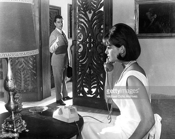 Philippe Nicaud watching Claudia Cardinale on the phone in a scene from the film 'The Magnificent Cuckold' 1964