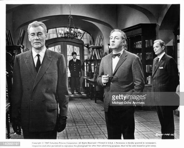 Philippe Noiret wearing a bowtie holding a pipe standing behind Peter O'Toole in a scene from the film 'Night Of The Generals' 1966