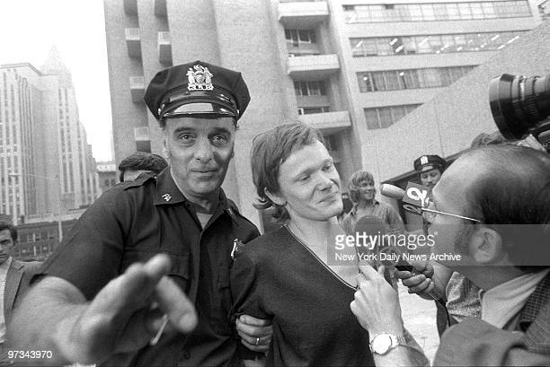 Philippe Petit answers reporter's questions as he is escorted from Beekman Hospital by Port Authority police officer Petit was arrested after he...
